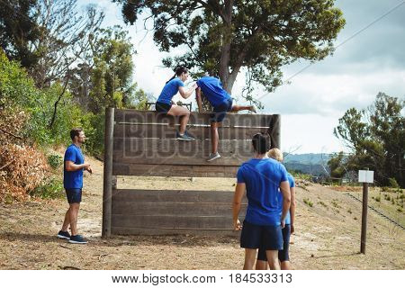 Female trainer assisting fit man to climb over wooden wall during obstacle course in bootcamp