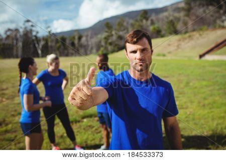 Portrait of fit man showing thumbs up in bootcamp