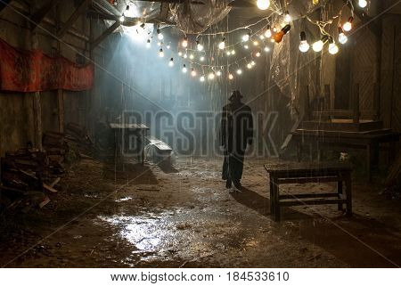 Silhouette of a man in a coat and hat in a dark alley on a rainy night