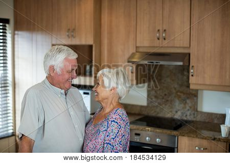 Happy senior couple looking at each other in kitchen at home