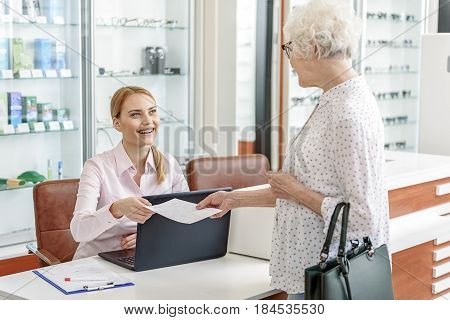 Happy smiling receptionist is taking necessary document, brought by client. She sitting near table in glasses shop