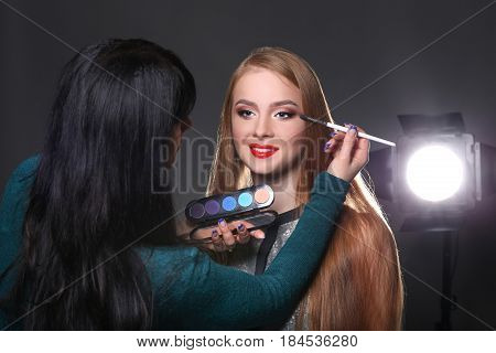 Backstage, fashion shooting. Make-up artist working with beauty model, applying eyeshadow palette, dark studio background