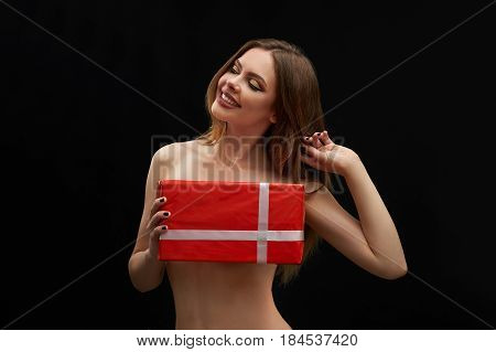 Gorgeous cheerful young woman posing topless covering her breasts with a gift box smiling joyfully with her eyes closed touching her hair flirtatiously on black background sexuality seduction surprise.
