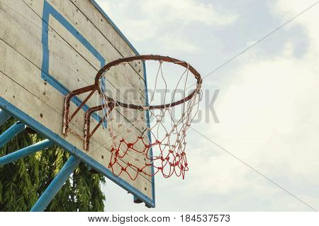 Old basketball hoop in the park and sky background