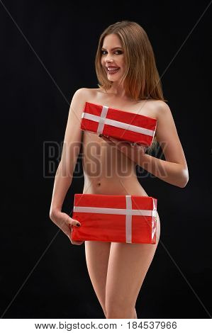 Stunning young nude woman with perfectly shaped toned body smiling posing on black background holding presents posing on dark background copyspace nudity sexuality erotic event celebrate mood festive.