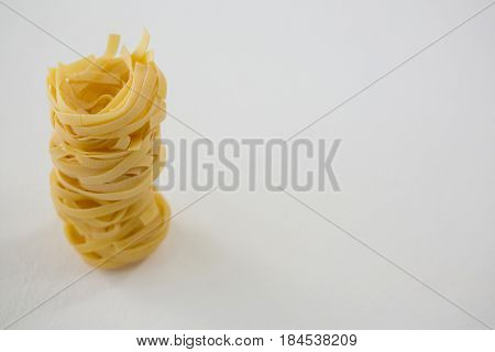 Stack of fettuccine pasta on white background