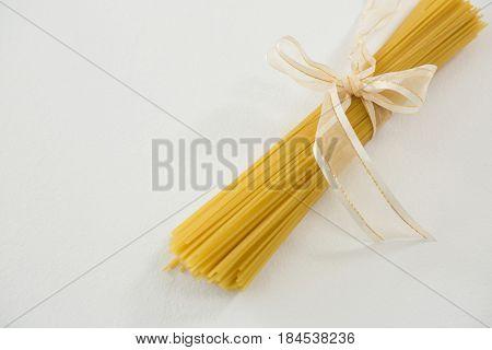 Bundle of raw spaghetti tied with white ribbon on white background