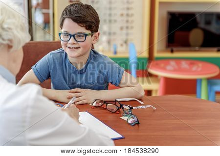 Happy smiling child wearing glasses is sitting near table afore doctor and looking at her with joy. Portrait