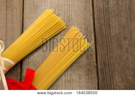 Bundles of raw spaghetti tied with ribbons on wooden surface