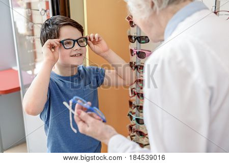 Hilarious little boy is wearing glasses and looking at optic store assistant with bright smile. Portrait