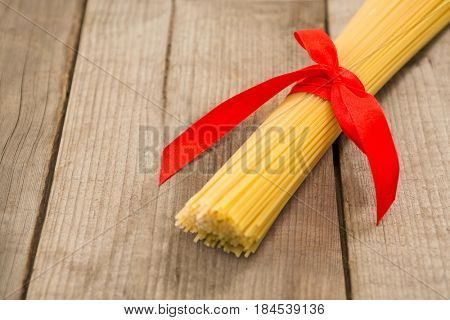Bundle of raw spaghetti tied with red ribbon on wooden surface