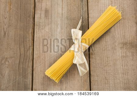 Bundle of raw spaghetti tied with white ribbon on wooden surface