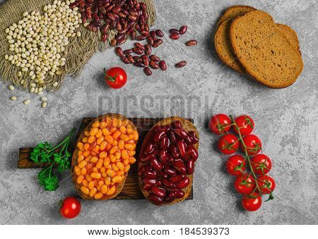Braised beans in tomato sauce on vegetarian sandwiches with bean. Open sandwiches with bread stewed white and red beans. Raw beans pieces of rye bread for sandwiches. Top view.