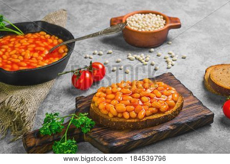Braised beans in tomato sauce in cast iron pan. Vegetarian sandwiches with bean. Open sandwiches with bread stewed white beans. Raw white beans pieces of rye bread for sandwiches. Gray stone background.