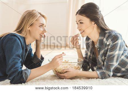 Women Lying On Carpet And Eating Popcorn