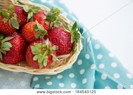 Close-up of fresh strawberries in wicker tray on white background