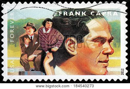 LUGA RUSSIA - APRIL 26 2017: A stamp printed by USA shows famous American film director Frank Capra and Clark Gable Claudette Colbert starring in comedy film It Happened One Night circa 2012