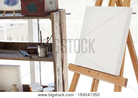 Easel with blank canvas in drawing room