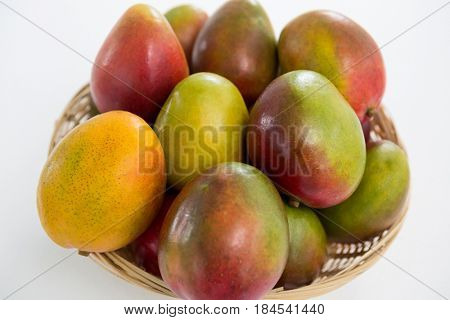 Close-up of red mangoes in wicker basket on white background
