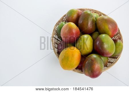 Overhead of red mangoes in wicker basket on white background