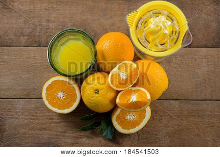 Overhead of oranges with glasses of juice and juicer on wooden table