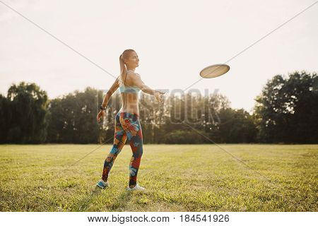 Young athletic girl playing with flying disc in the park. Professional player. Sport concept. Focus on flying disc