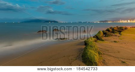 A long exposure view of Nha Trang bay just after sunset with moss covered rocks in the foreground and the city lights ablaze.