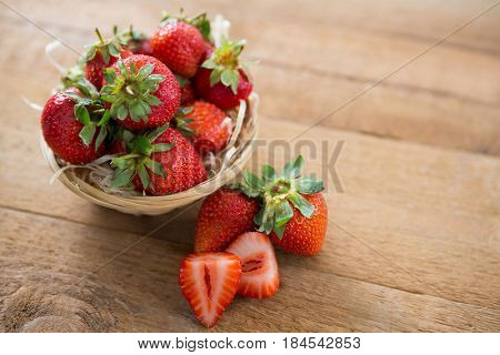 Fresh strawberries in wicker bowl on wooden table