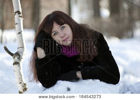 A girl in a fur coat walks through the winter forest, lying around and playing in the snow