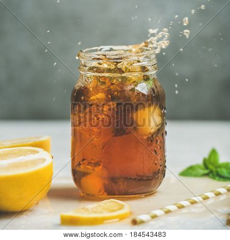 Summer cold Iced tea with fresh bergamot and mint in glass jar with splashes, grey concrete wall at background, copy space, square crop. Food in motion concept