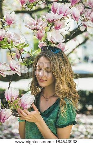 Young woman in casual clothes touching magnolia flowers under magnolia tree