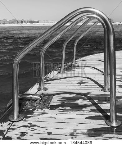 Smooth row Metallic chrome-plated Handrails railing on a yacht against the background of a sunny bright sky black and white photography.