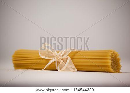 Bundle of raw spaghetti tied with white ribbon on napkin
