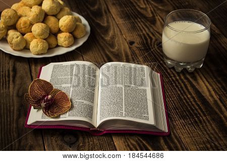 the bible cookies and milk on wooden background