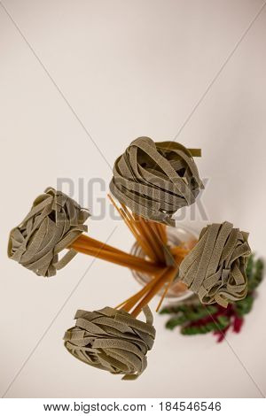 Spaghetti and fettuccine pasta arranged in shape of plant on white background