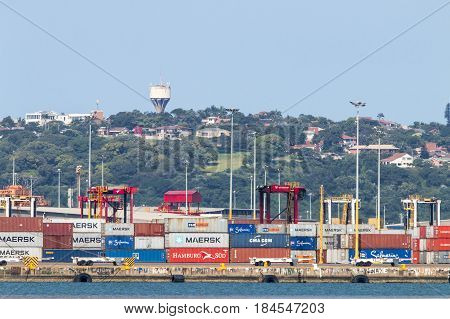 DURBAN SOUTH AFRICA - APRIL 9 2017: Containers stacked in Harbor on wharf against straddle carriers residential district on the Bluff in Durban South Africa