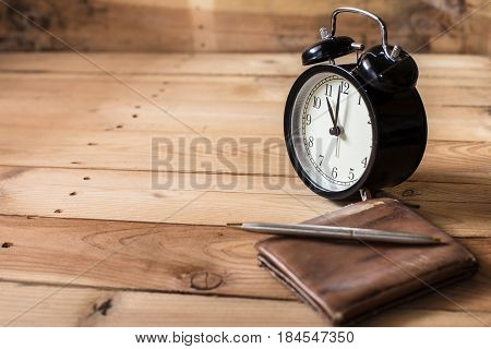 time to payment concept. retro bell clock timed at 11 o'clock on wood background with old leather wallet