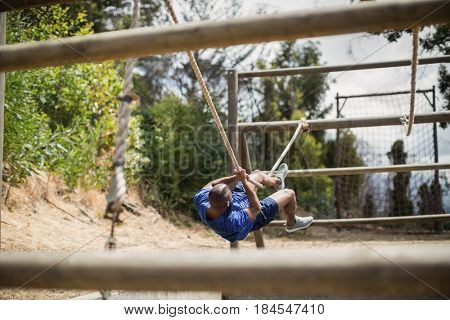 Man crossing the rope during obstacle course in boot camp