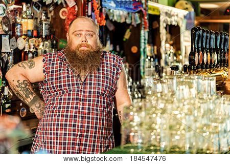 I am waiting my clients. Portrait of serene fat bartender situating at market stall in tap-room