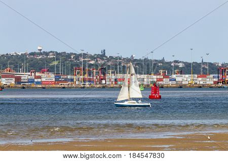 DURBAN SOUTH AFRICA - APRIL 9 2017: Single yacht at low tide in harbor against stacked containers and the Bluff in Durban South Africa