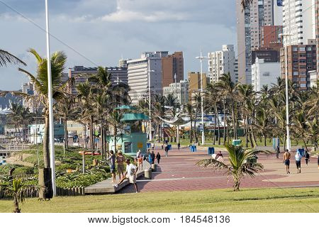 DURBAN SOUTH AFRICA ; APRIL18 2017; Early morning many unknown people on promenade against city skyline in Durban South Africa