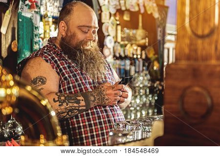 Funny fat bartender expressing gladness while looking at mobile phone. Different glasses and equipment locating near him