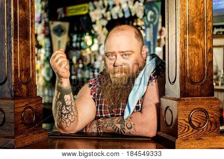I am waiting for my clients. Portrait of bearded man showing thoughtfulness while leaning on surface in boozer