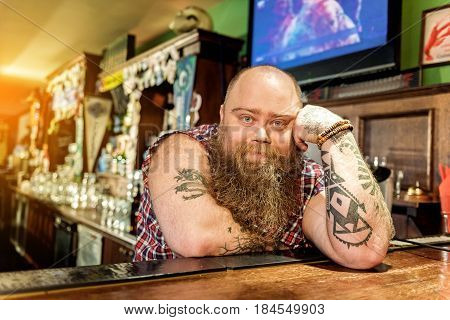 It is long hours during job. Portrait of calm bearded man showing boredom while leaning on counter in pub