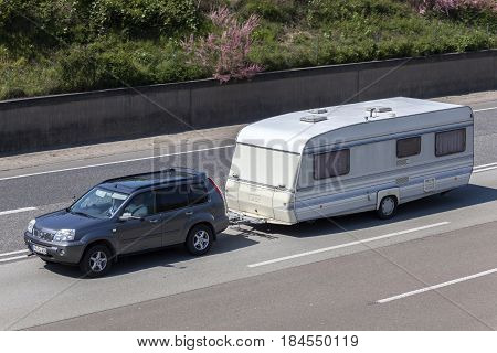 Frankfurt Germany - March 30 2017: Nissan x-trail towing a caravan on the highway in Germany