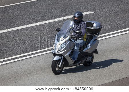Frankfurt Germany - March 30 2017: Man riding a Peugeot scooter on the highway in Germany