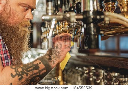 Serene fat man cleaning faucet after filling cup of ale from it