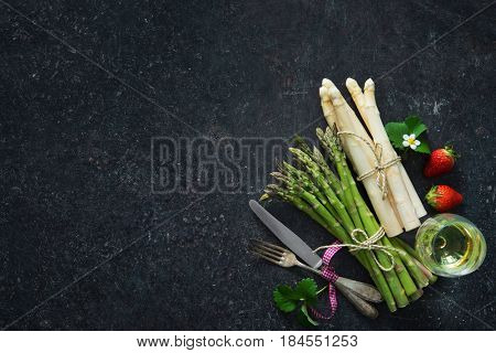 Fresh green and white asparagus with strawberries and wineglass on dark background