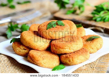 Small chickpea burgers on a plate. Fried vegan burgers made with chickpeas puree. Simple, nutritious and quick food idea. Rustic stile. Closeup