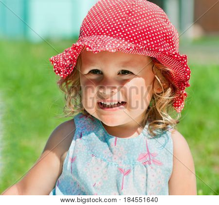 Portrait of smiling little girl in red sunhat outdoors